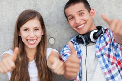 Teenage couple with thumbs up Stock Photography