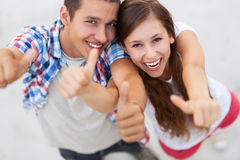 Teenage couple with thumbs up Stock Photo