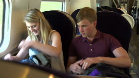 Teenage Couple Using Digital Devices On Train Journey. Teenage couple looking using e-reader and mobile phone whilst sitting at table on train journey.Shot on stock video