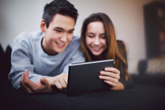 Teenage couple using digital tablet - Indoors Stock Photo