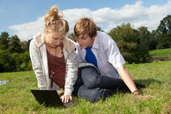 Teenage couple using laptop Royalty Free Stock Photos