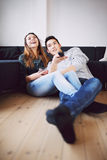 Teenage couple watching comedy show on TV Stock Photo