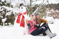 Teenage Couple In Winter Landscape Next To Snowman Royalty Free Stock Photography