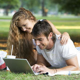 A teenage couple working on a laptop in a park Stock Photography