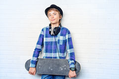 Teenage culture. Modern teenage boy with skateboard. Studio shot. Youth culture Stock Photos