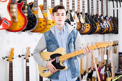 Teenage customer deciding on suitable amp in guitar shop Royalty Free Stock Photography