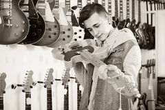 Teenage customer deciding on suitable amp in guitar shop Royalty Free Stock Photos