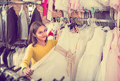 Teenage customer examining dresses in children's cloths shop Stock Images