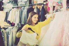 Teenage customer examining dresses in children's cloths shop Stock Photography