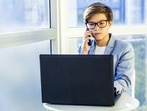 Teenage cute business boy with phone and computer in office Royalty Free Stock Photos