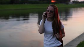Teenage cute girl talking on mobile phone outdoors evening during sunset. stock video footage