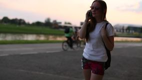 Teenage cute girl talking on mobile phone outdoors evening during sunset. stock video