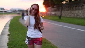 Teenage cute girl talking on mobile phone outdoors evening during sunset. stock footage