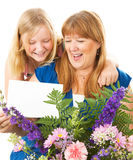 Mother and Daughter Mothers Day. Teenage daughter giving flowers and a card to her mother on Mother's Day.  Card blank ready for your text Royalty Free Stock Image