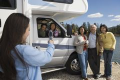 Teenage daughter photographing family with cell phone outside RV at lake Royalty Free Stock Photos