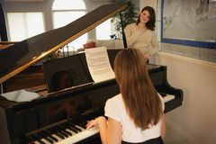 Teenage Daughter Playing The Piano For Her Mother Royalty Free Stock Images