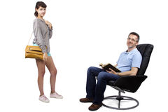 Teenage Daughter Saying Bye to Father. Teenage daughter leaving single father on a white background.  She looks like she is going out while dad sits on a chair Stock Images