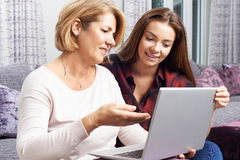Teenage Daughter Showing Mother How To Use Laptop Computer. Teenage Daughter Shows Mother How To Use Laptop Computer Royalty Free Stock Photography
