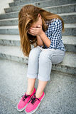 Teenage depression. Unhappy depressed teenager with face in hands sitting outdoor Royalty Free Stock Images