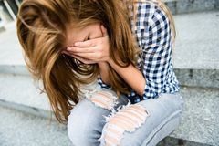 Teenage depression. Unhappy depressed teenager with face in hands sitting outdoor Stock Photos