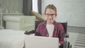 Teenage disabled girl in a wheelchair using a laptop and looking at the camera smiling