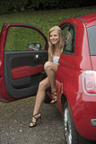 Teenage driver getting out of her car Royalty Free Stock Photo