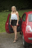 Teenage driver getting out of her car Stock Photography