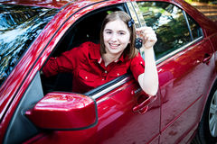 Teenage Driver in New Car. Teenage girl with her driver's license driving a new car and holding keys Royalty Free Stock Image