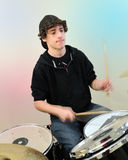 Teenage drummer in action. Teenage boy plays drums as hands and drum sticks blur Stock Image