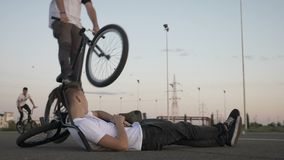 Teenage extreme biker performing bunny hop move jumping over his biker friend standing down in slow motion  -. Teenage extreme biker performing bunny hop move stock video footage