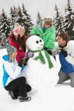 Teenage Family Building Snowman On Ski Holiday Royalty Free Stock Photography