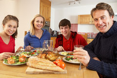 Teenage Family Eating Lunch Together In Kitchen. Smiling At Camera Stock Image
