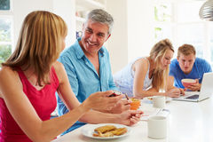 Teenage Family Having Breakfast In Kitchen With Laptop Royalty Free Stock Image