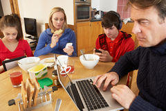 Teenage Family Using Gadgets Whilst Eating Stock Images
