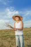 Teenage farmer holds bundle of straw Stock Images