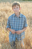 Teenage farmer standing among field of barley Stock Photo