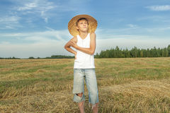 Teenage farmer standing on harvested field Royalty Free Stock Photo