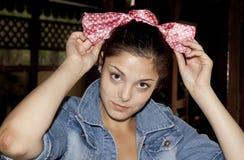Teenage Fashion. Vain teenage girl fixing hair bow Royalty Free Stock Photos