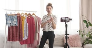 Teenage fashion vlogger presenting new outfit in front of mobile camera stock video