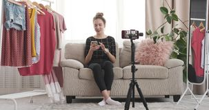 Fashion vlogger recording new video using mobile phone at boutique. Teenage fashion vlogger recording new video using mobile phone camera at her boutique stock video