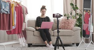 Fashion vlogger using laptop and speaking in front of mobile camera stock video footage