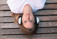 Teenage female listening music outdoor, lying on bench and relaxing? summer stock images