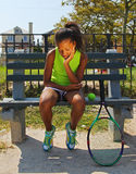 Teenage female tennis player. 13 year old girl sitting on bench, upset Stock Photos