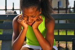 Teenage female tennis player. 13 year old girl sitting on bench, upset Royalty Free Stock Image