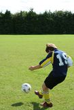 Teenage Footballer. Young teen kicks a football royalty free stock image