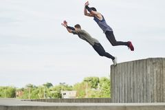 Teenage free runners jumping off concrete structure Royalty Free Stock Photo