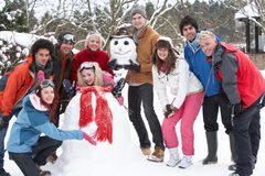 Teenage Friends Building Snowman In Garden Royalty Free Stock Photos