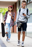Teenage friends carrying skateboards in the city Royalty Free Stock Image