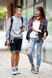 Teenage friends carrying skateboards in the city Stock Photo