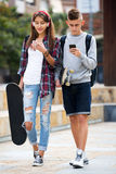 Teenage friends carrying skateboards in the city Stock Image